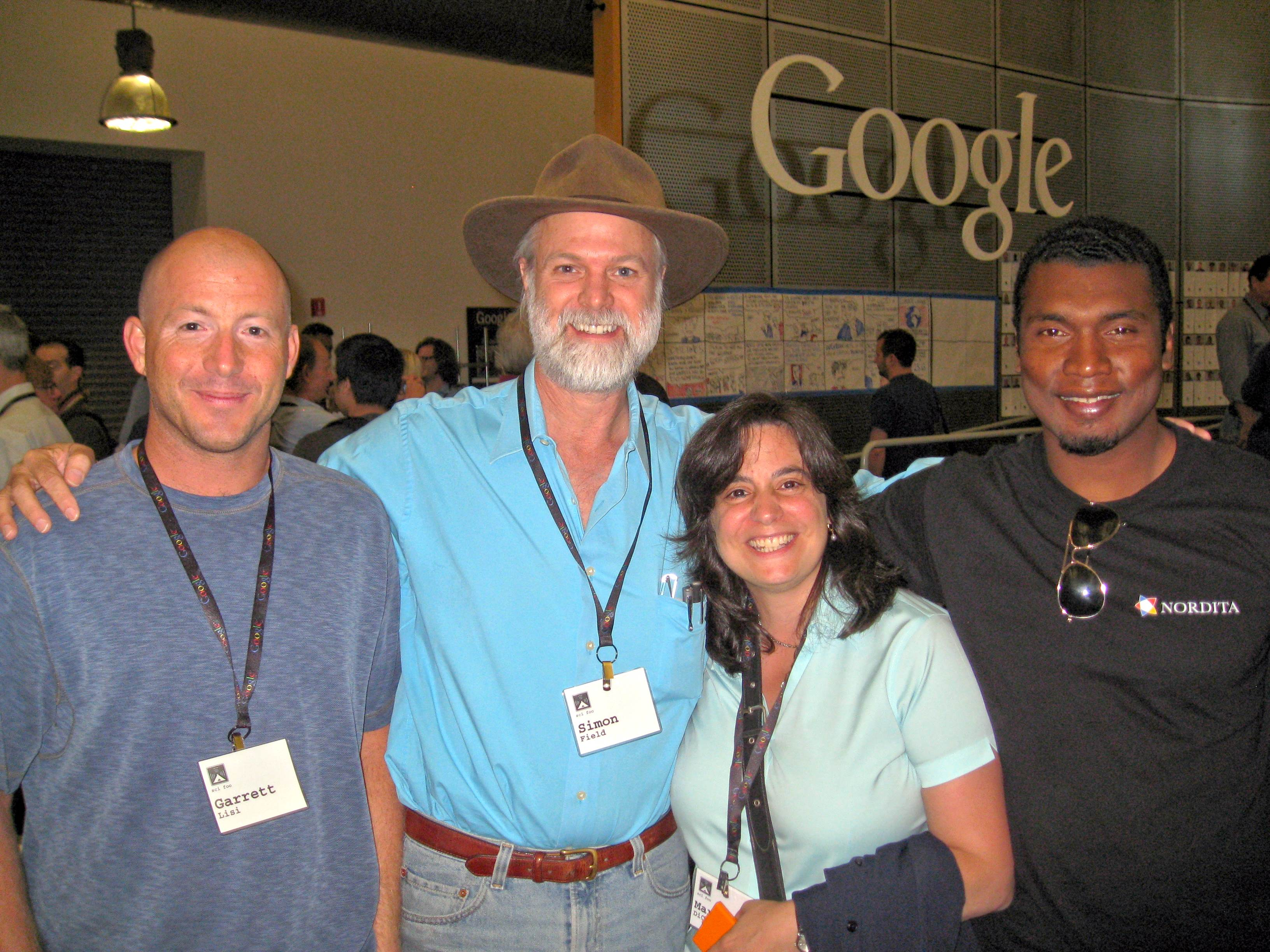 Physicist Garrett Lisi, executive editor of Scientific American Mariette DiChristina, and cosmologist Stephon Alexander, pose with Simon Field